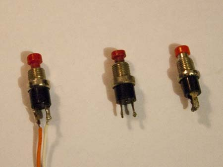 Three generic red push-button switches